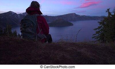 Tourist looking at Crater Lake Oregon Landscape - Backpacker...