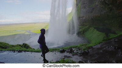 Tourist looking at spectacular waterfall iceland. Happy ...