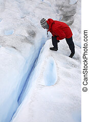An adventure tourist looking into a crevasse on the Perito Moreno Glacier in Patagonia in southern Argentina.