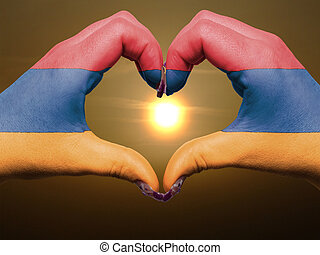 Tourist made gesture by armenia flag colored hands showing symbol of heart and love during sunrise