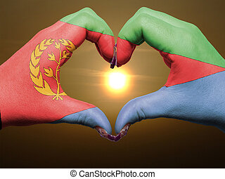 Tourist made gesture by eritrea flag colored hands showing symbol of heart and love during sunrise