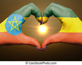 Tourist made gesture by ethiopia flag colored hands showing symbol of heart and love during sunrise