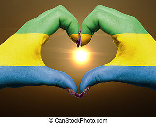 Tourist made gesture by gabon flag colored hands showing symbol of heart and love during sunrise