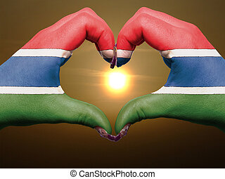 Tourist made gesture by gambia flag colored hands showing symbol of heart and love during sunrise
