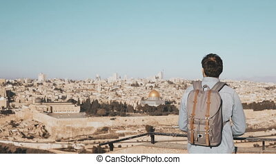 Tourist male takes photos of Jerusalem panorama. Man with backpack stands at skydeck edge with smartphone. Israel 4K.
