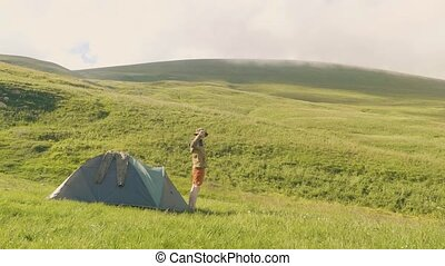 Tourist man came out of camping tent on green meadow and mountain background
