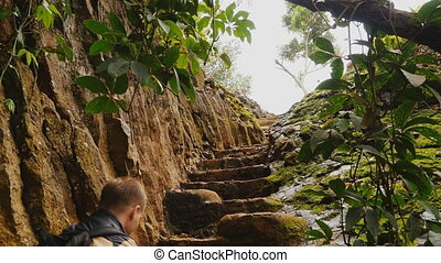 Tourist man climbing stairs into the rock. Beautiful nature. Vietnamese jungle near Elephant Falls.