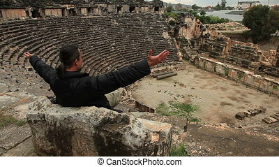Tourist man  influenced ancient  amphitheater and clapping