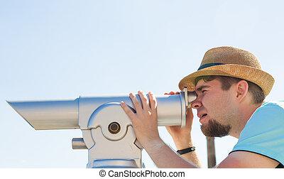 tourist man looks through the long binocular landscape