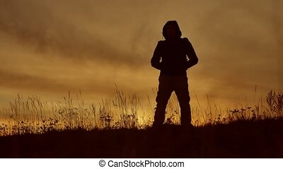 tourist man silhouette at sunset. sunlight man hooded travel...