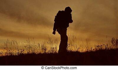 tourist man silhouette at sunset. sunlight man hooded travel...