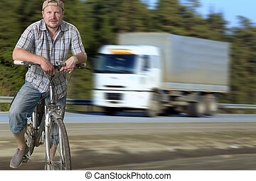Tourist man standing on the road with a bicycle
