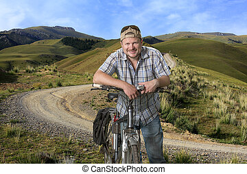 Tourist man standing with a bicycle in a highlands