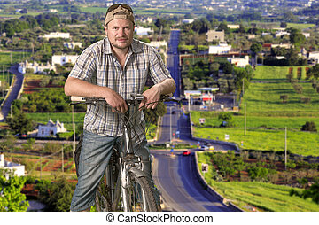 Tourist man standing with a bicycle on the countryside background