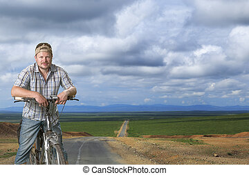 Tourist man standing with a bicycle on the road natural background