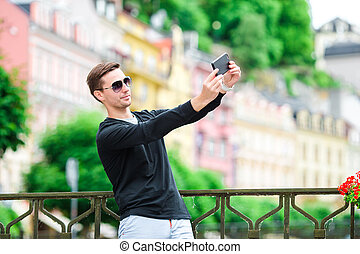 Tourist man taking travel photos with smartphone on summer holidays. Young attractive tourist taking selfie photo with mobile phone outdoors enjoying holidays travel destination in tourism.