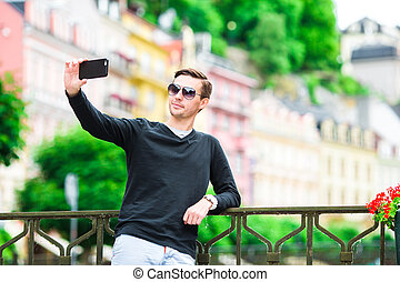 Tourist man taking travel photos with smartphone on summer holidays. Young attractive tourist taking selfie photo with mobile phone outdoors enjoying holidays travel destination in tourism and exploring concept