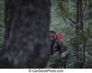 Tourist man with backpack in camouflage uniform walking through forest. Hunter exploring the territory, looking around.