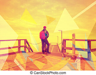 Tourist man with backpack on wooden pier above calm sea.