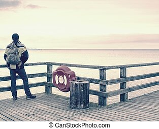 Tourist man with backpack on wooden pier