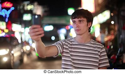 Tourist man with mobile phone takes picture in the night street with bokeh lights. 1920x1080