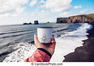 tourist mug in hand with the image of the mountains on the background of the sea