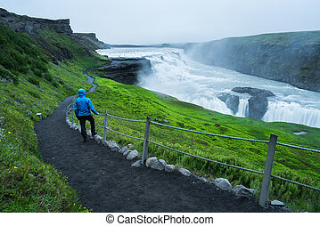 Tourist on a trip near the Gullfoss waterfall in Iceland -...