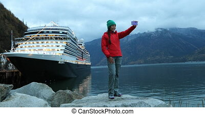 Tourist on Alaska cruise ship taking selfie photo in front of cruise ship in Skagway, Alaska, USA. Woman tourist taking picture using smart phone at night on travel vacation