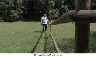 Tourist on meadow near wooden fence