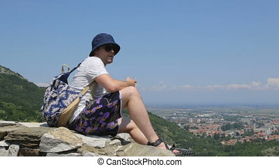 Tourist on stone wall in mountains
