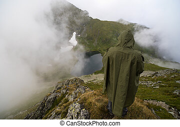 tourist on the mountain with a raincoat