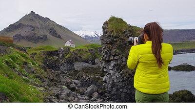 Tourist on travel taking photo with DSLR Camera, Iceland Arnarstapi Snaefellsnes