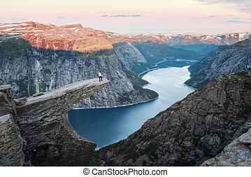 Tourist on Trolltunga rock in Norway mountains