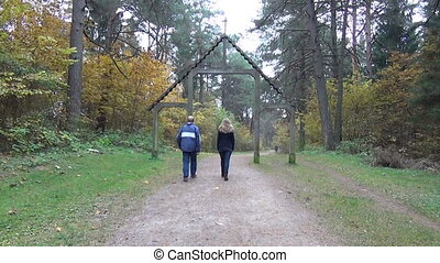 tourists woman and man go wide forest cognitive path reaches a large wooden ark