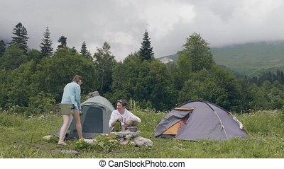 Tourist people eating and drinking while summer camping in mountain landscape