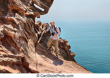 Tourist photographer climbs the cliff above sea, Hormuz Island, Iran.