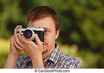 Tourist photographer with photo camera shooting in the park