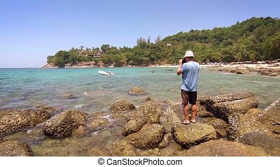 Tourist Photographing a Spectacular, Tropical Seascape from...
