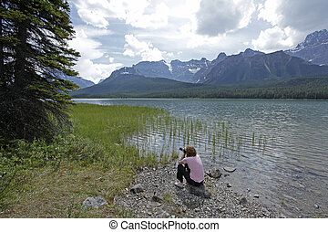 Tourist photographing Lake Louise in Banff National Park