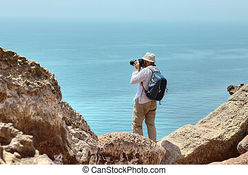 Tourist photographing nature, standing on the edge of a cliff.