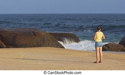 Tourist Photographing Seascape from Sandy Beach in Sri Lanka...