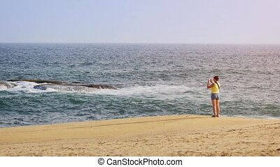 Tourist Photographing Sri Lankan Seascape from Sandy Beach -...