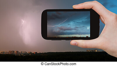 tourist photographs of lightning bolt over city