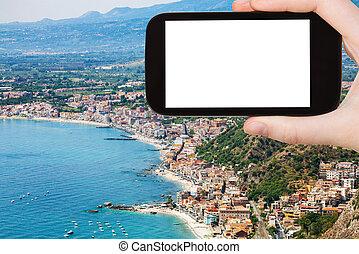 tourist photographs shore with Giardini Naxos - travel...