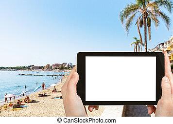 tourist photographs urban beach in Giardini-Naxos - travel...