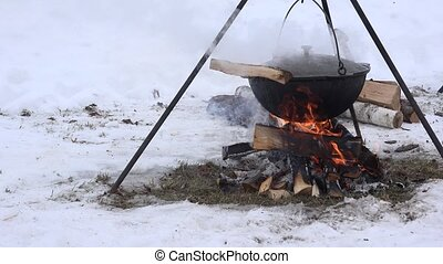tourist pot hang over fire in forest winter, over campfire.