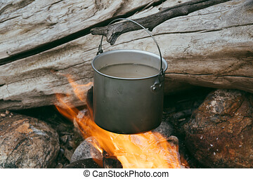 Tourist pot over the fire. Cooking in aluminum cookware. Survival in the wild.