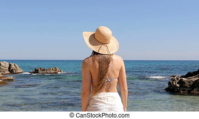 Tourist reaching the beach contemplating ocean on vacation -...