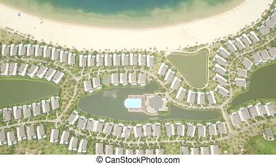 Tourist resort villas and hotels on sea shore drone view. Luxury cottage village with mansion and swimming pool on blue sea shore. Aerial landscape architecture tourist hotel on ocean coast.