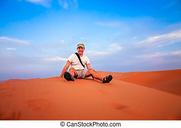 Tourist resting on the sand dunes of Merzouga